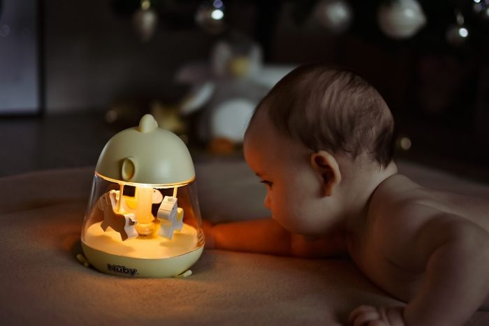 This image has an empty alt attribute; its file name is baby-with-musical-carousel-700x467.jpg